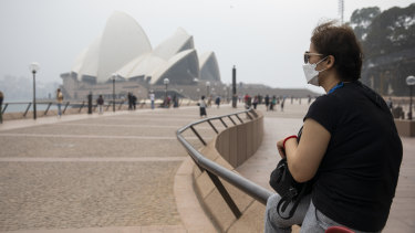 A woman wearing a face mask sits near a haze-shrouded Sydney Opera House.