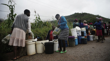 People queue for fresh water in Chimanimani, Zimbabwe on Saturday after Cyclone Idai caused floods that swept through Mozambique, Zimbabwe and Malawi.
