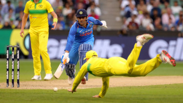 Near miss: Australia's Shaun Marsh attempts to run out India's MS Dhoni.
