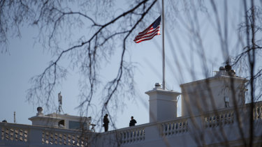 Members of the Secret Service look out from atop the White House on Sunday.