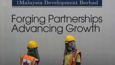 Construction workers chat in front of a billboard for state investment fund 1 Malaysia Development Berhad (1MDB) in Kuala Lumpur, Malaysia.