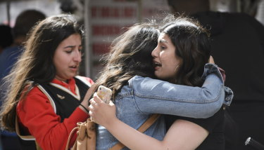 Friends embrace after shots were fired at the championship parade.