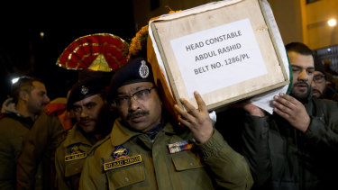 Indian police officers carry coffin of their colleague during a wreath-laying ceremony in Srinagar, Indian controlled Kashmir, on Monday.