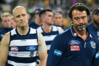 Defeated Geelong coach Chris Scott leads his players from the Gabba
