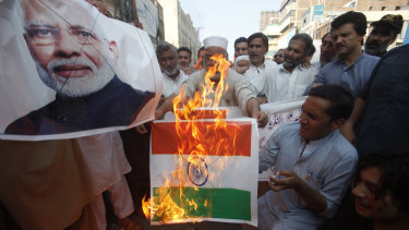 Pakistanis burn a representation of an Indian flag and a poster of Indian Prime Minster Narendra Modi in protest over the Kashmir decree.