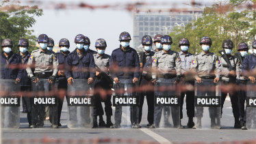 Police officers stand in a road blocking protesters during a demonstration in Mandalay.