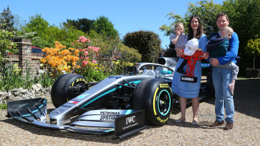 Harry Shaw, 5, who has been diagnosed with a rare form of bone cancer, is carried by father James with mother Charlotte and sister Georgia and a replica of Lewis Hamilton's Formula 1 car.