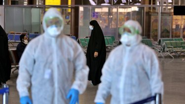 Medical staff prepare to check passengers arriving from Iran in the airport in Najaf, Iraq.
