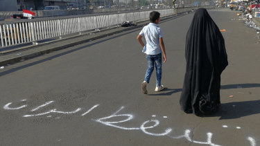 "People walk by an Arabic sentence writing on the asphalt reads ""Down with Iran"" near the site of the protests at Tahrir Square during anti-government protests in Baghdad."