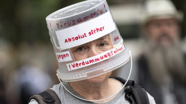 Demonstrator walks through Berlin-Charlottenburg with a plastic bucket placed on his head reading 'Absolutely safe against the stupidity virus', in Berlin.