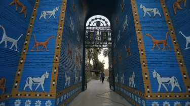 People walk near the replica Ishtar Gate the archaeological site of Babylon, Iraq, on Friday.
