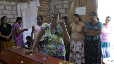A woman weeps standing beside the coffin with the remains of her 12-year old niece, Sneha Savindi.