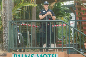 A policewoman stands guard outside the Palms Motel in Darwin.