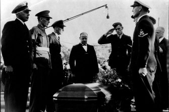 Sergeant John Curtin, only son of the late Prime Minister, salutes as the casket containing the body of his father is lowered into the grave at Karrakatta Cemetery, Perth.