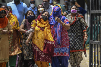 Distraught women outside a New Dehli hospital. Coronavirus cases and deaths in India are rising.