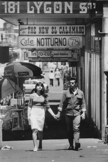 Young man and woman walking hand-in-hand along Lygon Street, Carlton in 1985.