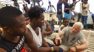 Actor Richard Gere, right, talks with migrants aboard the Open Arms Spanish humanitarian boat last week.