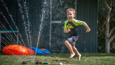 Cooper Bond, 5, of Jerrabomberra plays with water in the backyard earlier in January in a bid to cool off.