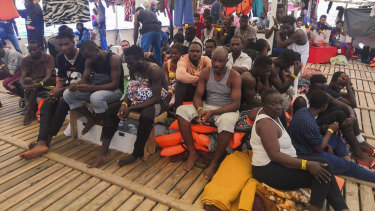 Migrants wait aboard the Open Arms Spanish humanitarian boat in the Mediterranean sea.