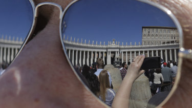 The Apostolic palace is reflected on the sunglasses of a man as faithful gather in St. Peter's Square during Pope Francis' Angelus noon prayer at the Vatican.