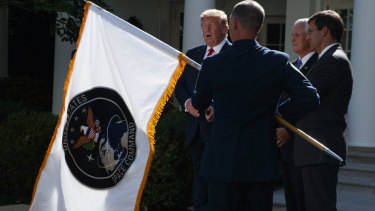US President Donald Trump watches as the flag of the new US Space Command is presented.