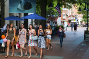 Charlottesville, Virginia, USA - June 7, 2012: Four young ladies, two carrying shopping bags and two carrying ice cream cones, are among the people on a summer day walking at the Downtown Mall, a pedestrian area in the center of Charlottesville. The photograph hanging above the girls, part of an outdoor exhibit for the LOOK3 Festival, is by David Doubilet. sataug17charlottesville Charlottesville Virginia USA ; text by Lance Richardson ; iStock *** REUSE PERMITTED ***