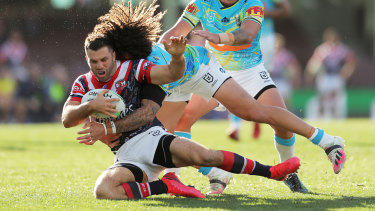 Tedesco is tackled by Kevin Proctor during the Roosters' win over the Titans.