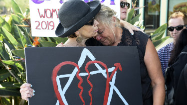 Leslie Gollub and Gretchen Gordon hug at a vigil held to support the victims.