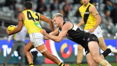 Caught short: Port Adelaide's Peter Ladhams runs down Richmond's Derek Eggmolesse-Smith.