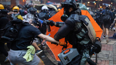 Riot police use pepper spray against protesters.