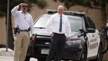 Columbine High School principal Scott Christy, right, watches as students leave the school on Tuesday.