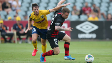 Mariners' Tommy Oar goes through the back of Wanderers debutant Simon Cox.