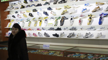 A guide stands in a showroom at the Ryuwon Shoe Factory in Pyongyang.