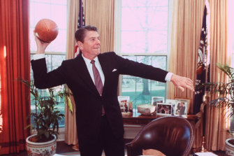 President Ronald Reagan throwing a football from his desk in the Oval Office.