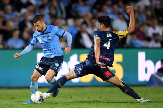 Sydney FC's Kosta Barbarouses tries to evade Eunsun Kim of the Mariners on Saturday night.