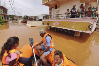 People stranded on a balcony in flood waters watch as others are rescued at Kolhapur in western Maharashtra state.