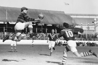 Yugoslavia's brilliant goalkeeper Vladimir Beara seldom takes a ball with his feet on the ground. Here he goes up for a shot while Australians Gordon Nunn and Harry Robertson (No. 10) move in. September 10, 1949