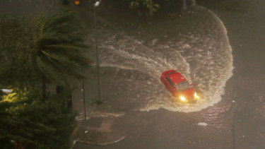 A vehicle negotiates a flooded street in Manila before dawn on Saturday.