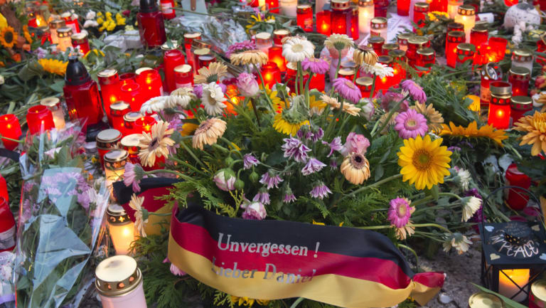 """Flowers, candles and a flag saying """"Unforgotten, Dear Daniel"""" sit at the scene of an altercation in Chemnitz, Germany, where a 35-year-old German of Cuban descent man was killed in an altercation with migrants."""
