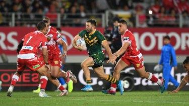 James Tedesco tries to evade Tongan defenders at Eden Park on Saturday night.