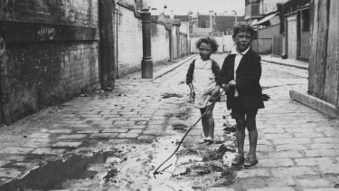 Entrance to a slum pocket known as Carlow Place, Carlton. The children are playing in runoff from a stable.