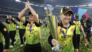 Alyssa Healy celebrates with the World Cup trophy.