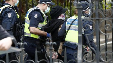 A woman is detained by Victoria Police on August 09, 2020.