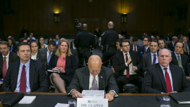 January 2017: James Comey,   then director of the FBI (left), James Clapper, then director of national intelligence (centre) and then CIA director John Brennan prepare to testify during a Senate hearing on Russian intelligence activities.