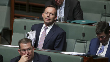 Tony Abbott watches on.