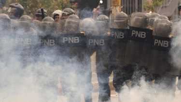 Economic chaos: Riot police stand amid tear gas as they face off with student protesters from the Venezuela Central University in November.