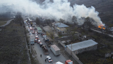 Smoke rises from a burning house as cars and trucks stuck in a huge traffic jam climbing along the road from Kalbajar leaving the separatist region of Nagorno-Karabakh to Armenia.
