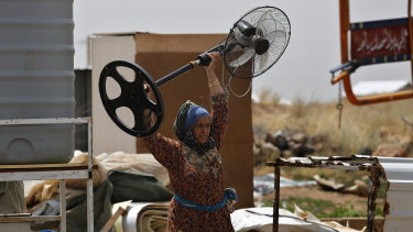 A Syrian woman carries a fan as she removes her belongings amid the evacuation of an informal refugee camp in Deir Al-Ahmar, Lebanon on Sunday.