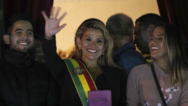 Bolivia's second Senate Vice-President and opposition politician Jeanine Anez, centre, wearing the Presidential sash, addresses the crowd from the balcony of the Quemado palace in La Paz after declaring herself interim president.
