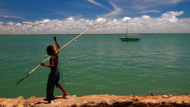 A boy with a fish spear walks along a sea wall at Saibai Island in the Torres Strait.
